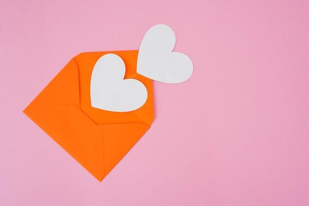 Twee witte harten en een envelop op een roze achtergrond met kopieerruimte.