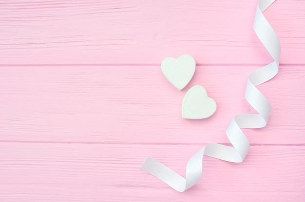 Twee witte harten en lint op roze houten achtergrond. valentijn dating ontwerp