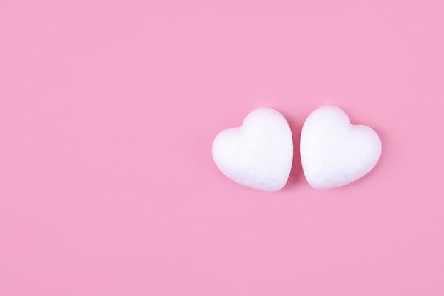 Twee witte harten op een roze achtergrond. hou van bovenaanzicht.