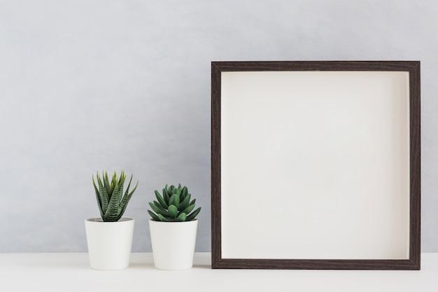 Twee witte ingemaakte cactusinstallatie met leeg wit fotokader op bureau tegen muur