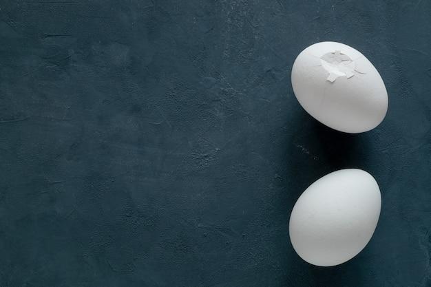 Twee witte kippeneieren - geheel en met gebroken gebarsten schelpen - op een donkere tafel
