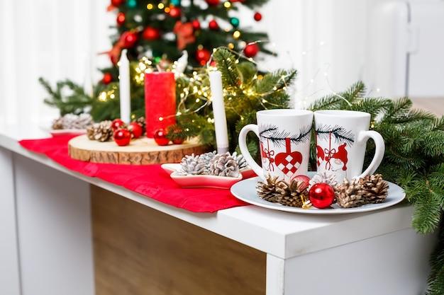 Twee witte koffiekopjes op de keukentafel tegen de achtergrond van kerstversiering. stukjes op een bord