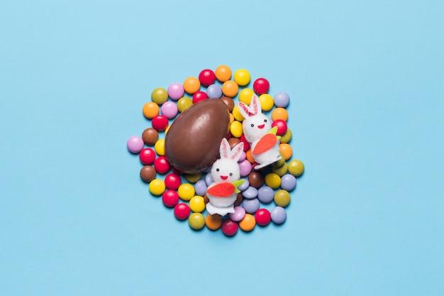 Twee witte konijntjes en chocoladepaasei op kleurrijk gemuikergoed tegen blauwe achtergrond