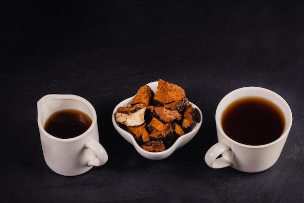 Twee witte kopjes helende koffie van berk paddestoel chaga met chaga stukken op zwart met kopie ruimte.