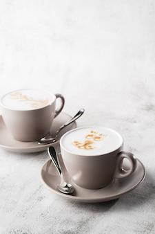 Twee witte kopjes hete latte koffie met mooie melk schuim latte kunst textuur geïsoleerd op heldere marmeren achtergrond. bovenaanzicht, kopieer ruimte. reclame voor café-menu. coffeeshop menu. horizontaal