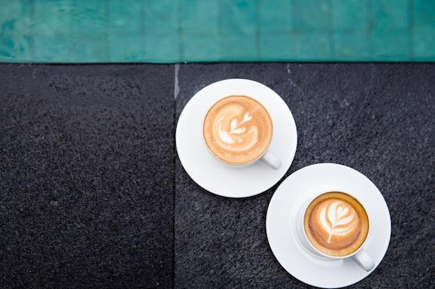 Twee witte kopjes lekkere cappucino met art latte aan de rand van het zwembad. vakantie tijd concept.