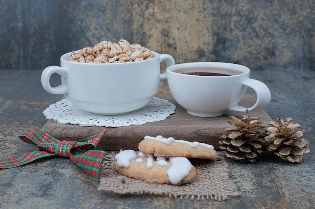 Twee witte kopjes met kerstkoekjes en twee dennenappels op een houten bord.