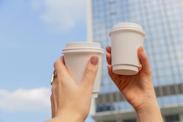 Twee witte kopjes met koffie om te gaan in vrouwelijke handen tegen de achtergrond van stadsgebouwen en de lucht