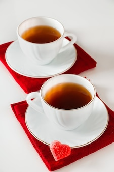 Twee witte kopjes thee op een witte achtergrond. hartvormige marmelade, symbool van valentijnsdag