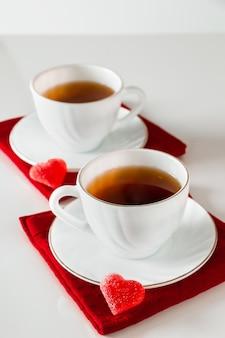 Twee witte kopjes thee op een witte achtergrond.