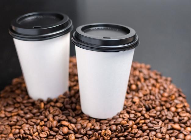 Twee witte kopjes warme koffie op een donkere ondergrond met koffiebonen