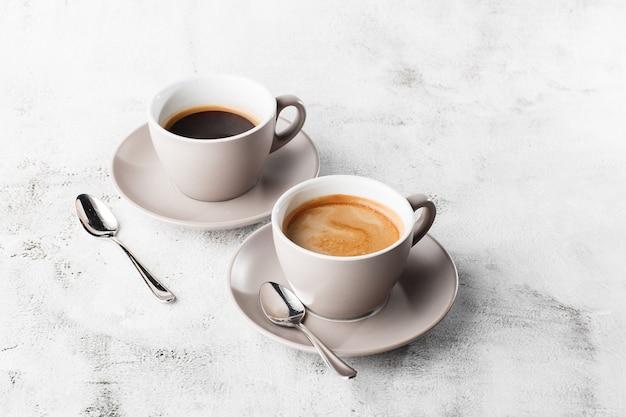 Twee witte kopjes warme zwarte koffie met melk geïsoleerd op lichte marmeren achtergrond. bovenaanzicht, kopieer ruimte. reclame voor café-menu. coffeeshop menu. horizontale foto.