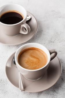 Twee witte koppen hete zwarte koffie met melk die op heldere marmeren achtergrond wordt geïsoleerd