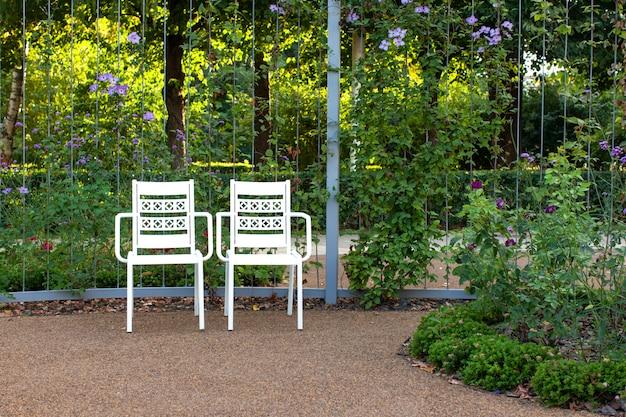 Twee witte lege ijzeren stoelen staan in een verlaten park met prachtige bloembedden. 's avonds schijnt de zonsondergangzon door de bomen.