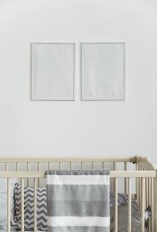 Twee witte lege muur frames boven babybedje babybedje met grijze deken
