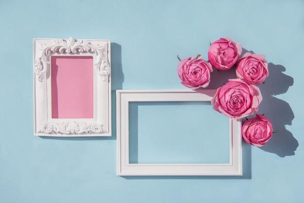 Twee witte lijsten met roze rozenbloemen op lichtblauwe achtergrond