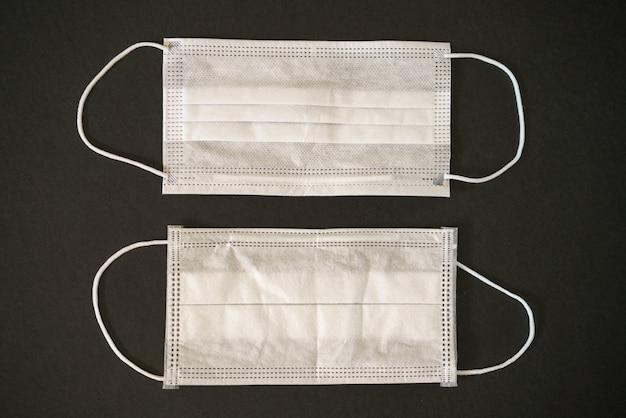 Twee witte medische maskers op een zwarte tafel