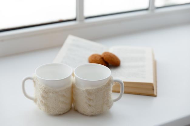 Twee witte mokken in een sjaal staan op een tafel op de achtergrond van een raam.