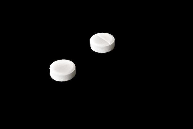 Twee witte pillen geïsoleerd op zwarte achtergrond.