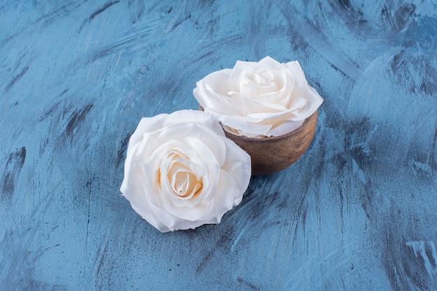 Twee witte rozen in houten kom op blauw.