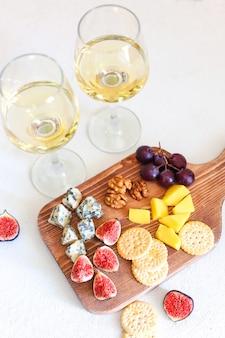 Twee witte wijnglas en kaasplank met noten