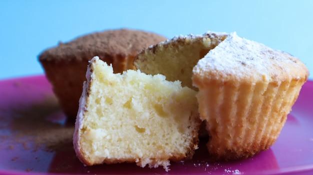 Twee wrongelcakes bestrooid met chocolade en poedersuiker op een roze bord, op een blauwe achtergrond. dessert, een kleine cupcake. witgebakken koekjes met een luchtige structuur. voedselconcept.
