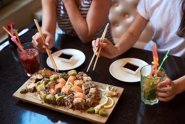 Twee yang-meisjes eten heerlijke rollende sushi in een restaurant dat op het houten bord wordt geserveerd