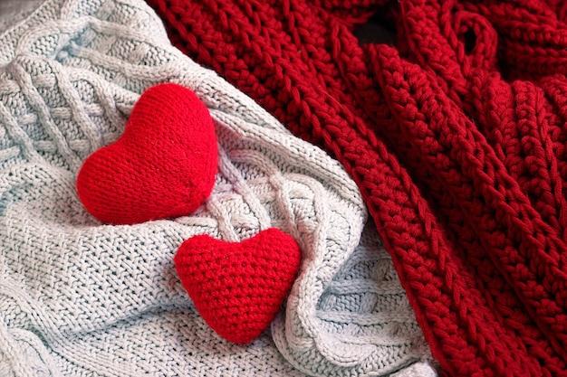 Twee zachte gebreide rode harten die samen op witte en rode gebreide dekenplaid liggen. gelukkig valentijnsdag concept. ruimte kopiëren