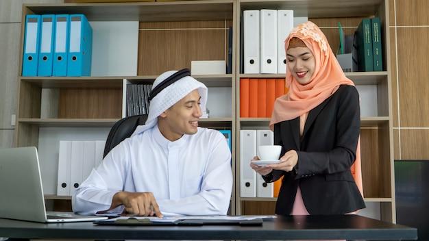 Twee zakelijke moslim collega's werken samen in een modern kantoor.