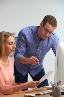 Twee zakelijke partners bespreken bedrijfsstatistieken met behulp van het papierwerk