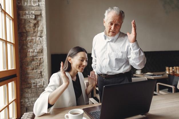 Twee zakelijke partners werken met een laptop in een café