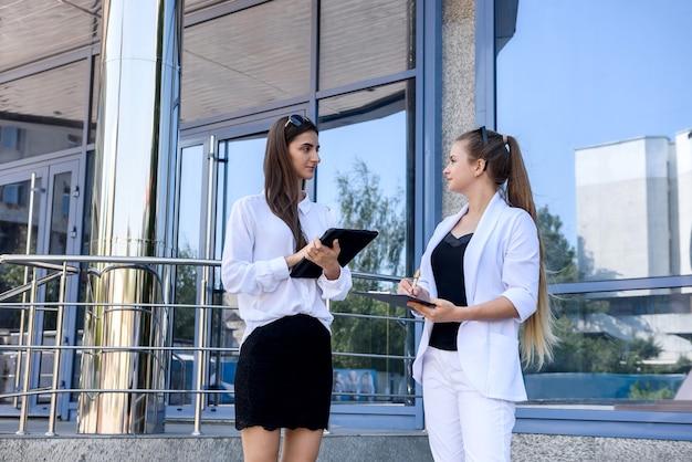 Twee zakelijke vrouwen bespreken enkele vragen buiten het kantoorgebouw