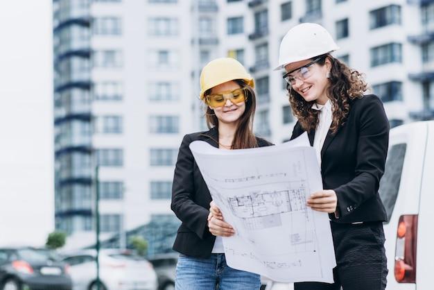 Twee zakelijke vrouwen in beschermende helmen en veiligheidsbril kijken naar bouwschema's, architectonisch concept