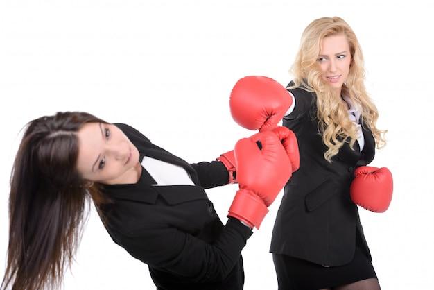 Twee zakelijke vrouwen met bokshandschoenen vechten.