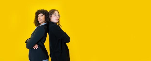 Twee zakelijke vrouwen zwarte spaanse en blanke kijken naar de camera met een zelfverzekerde uitdrukking op grote gele kopie ruimte - optimistisch werkende mensen in kantoorkleding samenwerken