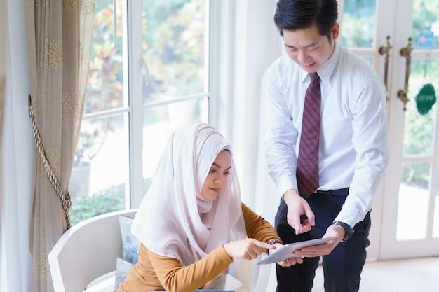 Twee zakelijke wijsvinger aan elkaar boven tablet op vergadering of onderhandeling op kantoor.