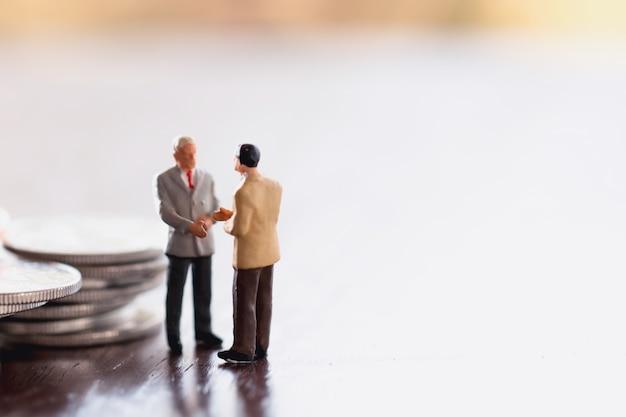Twee zaken man, opslaan, investeringen en financiã «n concepten. miniatuur mensen staan