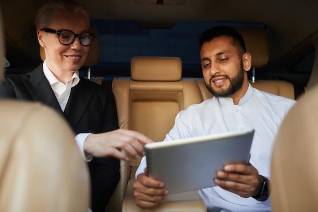 Twee zakencollega's die online op digitale tablet in team werken terwijl zij met de auto reizen