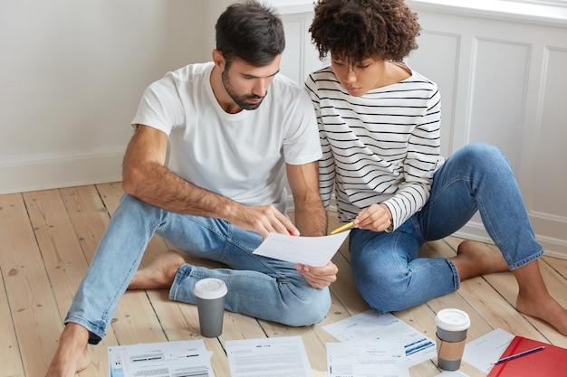 Twee zakencollega's van gemengd ras zitten op de vloer, brainstormen samen, houden de afdruk met informatie vast