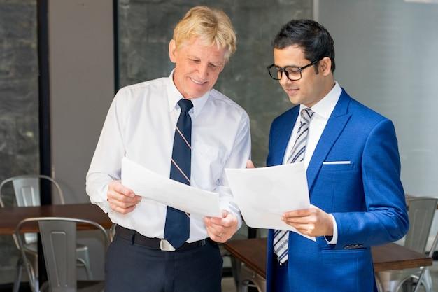 Twee zakenlieden die documenten herzien