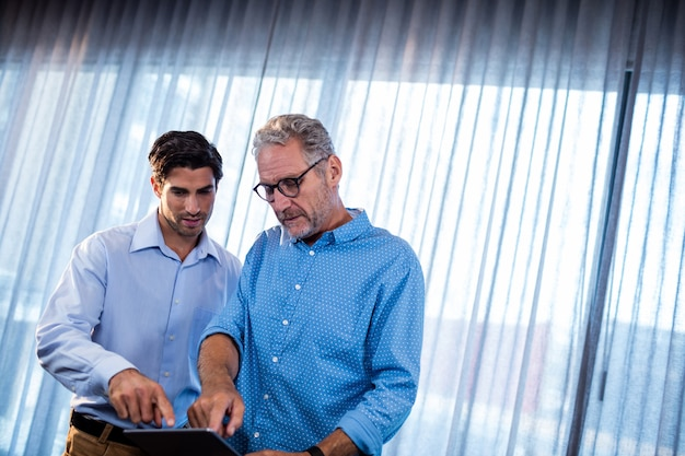 Twee zakenlieden die een tabletcomputer met behulp van