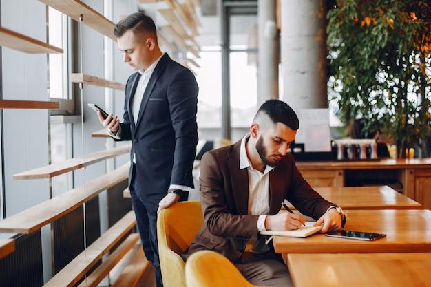 Twee zakenlieden die in een koffie werken