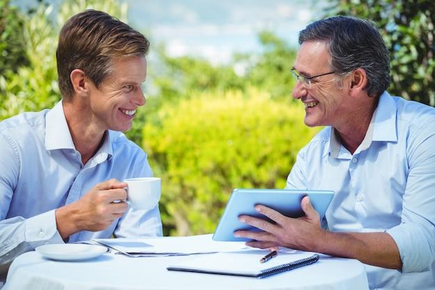Twee zakenlieden die in een restaurant samenkomen die tablet gebruiken