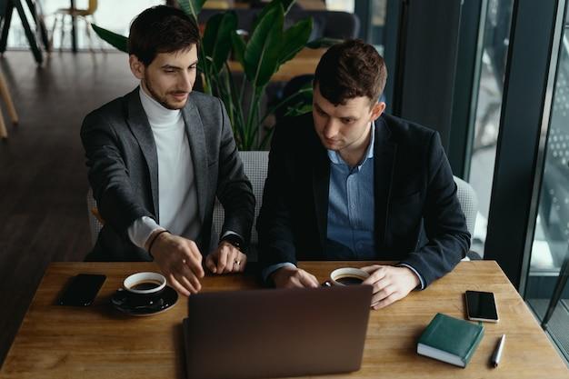 Twee zakenlieden die laptop het scherm richten terwijl het bespreken