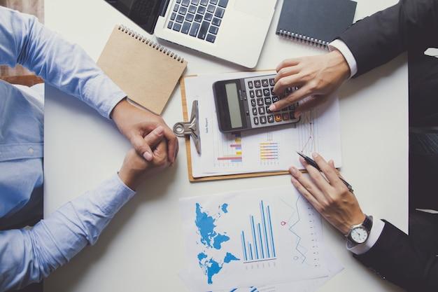 Twee zakenlieden die over in aanmerking komende investering spreken, manager die financieel rapport voorstelt dat goede werkresultaten toont aan tevreden baas