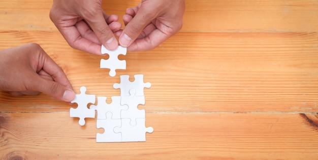 Twee zakenlieden die puzzel samen assembleren
