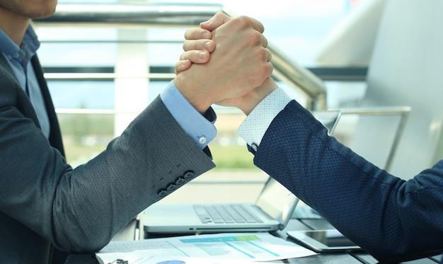 Twee zakenlieden drukken elkaar de hand op een voorwaartse achtergrond.