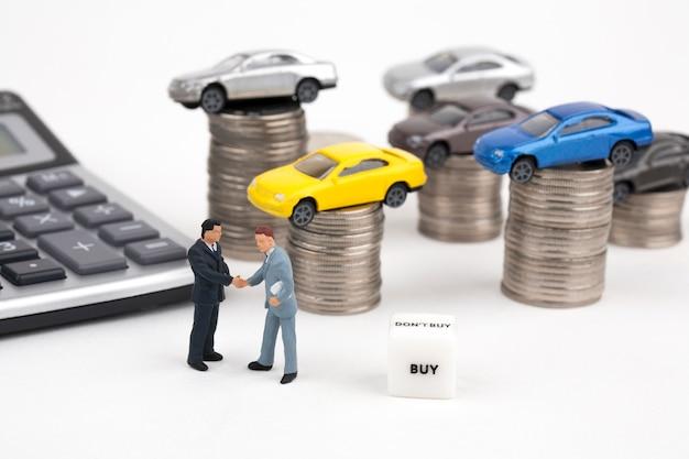 Twee zakenlieden en auto bovenop stapel muntstukken