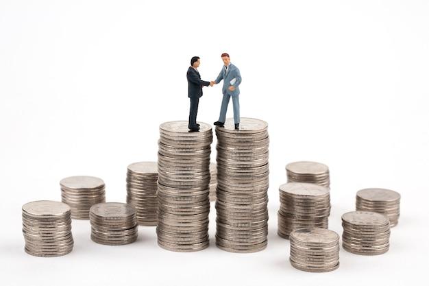 Twee zakenlieden handdruk bovenop stapel munten
