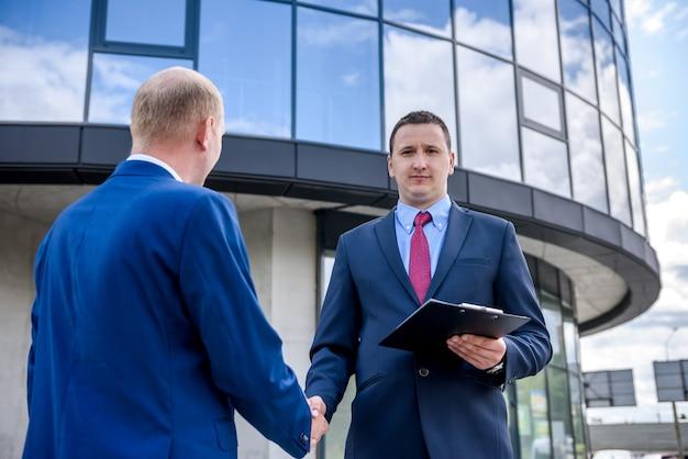 Twee zakenlieden handenschudden tegen nieuw gebouw
